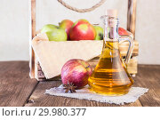 Купить «Processing of an agricultural crop of red and green apples. Homemade preparations, healthy diet vegetarian food. Spiced apple cider vinegar, juice, cider in a glass jug next to a box of ripe fruit», фото № 29980377, снято 16 февраля 2019 г. (c) Светлана Евграфова / Фотобанк Лори