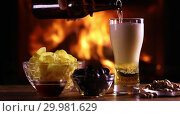 Купить «A man's hand pours light beer from a bottle into a glass on the background of a burning fireplace. Next to a glass of beer on the table are chips, olives and nuts», видеоролик № 29981629, снято 18 февраля 2019 г. (c) Алексей Кузнецов / Фотобанк Лори