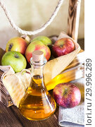 Купить «Processing of an agricultural crop of red and green apples. Home canning, healthy diet vegetarian food. Spiced apple cider vinegar, juice, cider in a glass jug next to a box of ripe fruit», фото № 29996289, снято 16 февраля 2019 г. (c) Светлана Евграфова / Фотобанк Лори