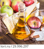 Купить «Processing of an agricultural crop of red and green apples. Home canning, healthy diet vegetarian food. Spiced apple cider vinegar, juice, cinnamon cider in a glass jug next to a crate of ripe fruit», фото № 29996297, снято 16 февраля 2019 г. (c) Светлана Евграфова / Фотобанк Лори