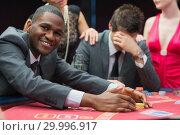 Купить «Man smiling while claiming jackpot», фото № 29996917, снято 20 июля 2012 г. (c) Wavebreak Media / Фотобанк Лори