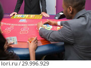 Купить «Man grabbing chips at poker table», фото № 29996929, снято 20 июля 2012 г. (c) Wavebreak Media / Фотобанк Лори