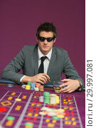 Купить «Man wearing sun glasses at roulette table», фото № 29997081, снято 20 июля 2012 г. (c) Wavebreak Media / Фотобанк Лори