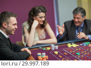 Купить «Men and woman talking at craps game», фото № 29997189, снято 20 июля 2012 г. (c) Wavebreak Media / Фотобанк Лори