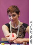 Купить «Woman at table holding dices», фото № 29997245, снято 20 июля 2012 г. (c) Wavebreak Media / Фотобанк Лори