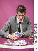 Купить «Man playing poker in a casino», фото № 29997289, снято 20 июля 2012 г. (c) Wavebreak Media / Фотобанк Лори