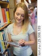 Купить «Woman standing at a bookshelf with tablet pc», фото № 29998189, снято 25 июля 2012 г. (c) Wavebreak Media / Фотобанк Лори