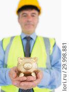 Купить «Smiling architect holding piggy bank», фото № 29998881, снято 31 июля 2012 г. (c) Wavebreak Media / Фотобанк Лори