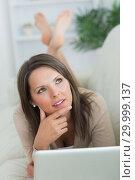 Купить «Thoughtful woman lying on the sofa with her laptop», фото № 29999137, снято 16 августа 2012 г. (c) Wavebreak Media / Фотобанк Лори