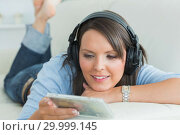 Купить «Happy woman listening music looking at cd on sofa», фото № 29999145, снято 16 августа 2012 г. (c) Wavebreak Media / Фотобанк Лори