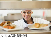 Купить «Chef handing dinner plates through order station», фото № 29999469, снято 1 августа 2012 г. (c) Wavebreak Media / Фотобанк Лори