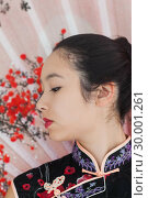 Купить «Serene woman wearing traditional Asian clothing», фото № 30001261, снято 23 августа 2012 г. (c) Wavebreak Media / Фотобанк Лори