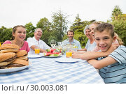 Extended family having dinner outdoors at picnic table. Стоковое фото, агентство Wavebreak Media / Фотобанк Лори
