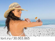 Attractive brunette with straw hat putting on sun cream. Стоковое фото, агентство Wavebreak Media / Фотобанк Лори