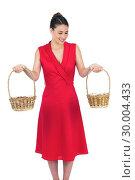 Купить «Content glamorous model in red dress holding baskets», фото № 30004433, снято 17 апреля 2013 г. (c) Wavebreak Media / Фотобанк Лори