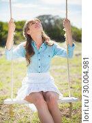 Купить «Young model relaxing while sitting on swing», фото № 30004981, снято 26 апреля 2013 г. (c) Wavebreak Media / Фотобанк Лори