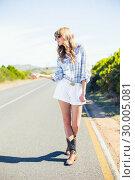 Купить «Trendy sexy blonde hitchhicking at the roadside», фото № 30005081, снято 26 апреля 2013 г. (c) Wavebreak Media / Фотобанк Лори