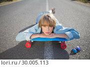 Купить «Funky young blonde lying on a road winking at camera», фото № 30005113, снято 26 апреля 2013 г. (c) Wavebreak Media / Фотобанк Лори