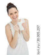 Купить «Cheerful model in white dress holding mug of coffee», фото № 30005297, снято 21 мая 2013 г. (c) Wavebreak Media / Фотобанк Лори