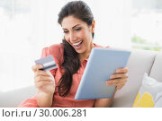 Купить «Excited brunette sitting on her sofa using tablet to shop online», фото № 30006281, снято 13 июня 2013 г. (c) Wavebreak Media / Фотобанк Лори