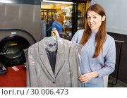 Купить «Portrait of cheerful female laundry customer holding clean clothes on hanger», фото № 30006473, снято 22 января 2019 г. (c) Яков Филимонов / Фотобанк Лори