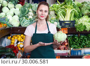 Купить «Smiling seller woman is demonstraiting cabbage in the market.», фото № 30006581, снято 29 апреля 2018 г. (c) Яков Филимонов / Фотобанк Лори