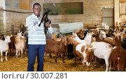 Купить «African American owner of goat farm with little goats», фото № 30007281, снято 15 декабря 2018 г. (c) Яков Филимонов / Фотобанк Лори