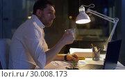 Купить «businessman with papers and coffee at night office», видеоролик № 30008173, снято 11 февраля 2019 г. (c) Syda Productions / Фотобанк Лори