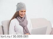 Купить «Cheerful cute brunette with winter hat on using her laptop», фото № 30009081, снято 22 мая 2013 г. (c) Wavebreak Media / Фотобанк Лори