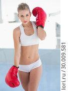 Severe young blonde model wearing boxing gloves. Стоковое фото, агентство Wavebreak Media / Фотобанк Лори