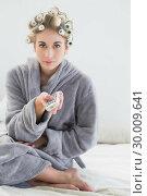 Купить «Lovely relaxed blonde woman in hair curlers using a remote control», фото № 30009641, снято 6 июня 2013 г. (c) Wavebreak Media / Фотобанк Лори