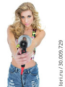 Купить «Unsmiling retro blonde woman pointing a hair dryer to the camera», фото № 30009729, снято 6 июня 2013 г. (c) Wavebreak Media / Фотобанк Лори