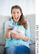 Купить «Woman sitting on sofa screaming while watching tv», фото № 30010141, снято 9 мая 2013 г. (c) Wavebreak Media / Фотобанк Лори