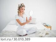 Купить «Serious blonde looking at reflection on cosy bed», фото № 30010389, снято 11 июня 2013 г. (c) Wavebreak Media / Фотобанк Лори