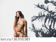 Купить «Sexy woman in flowery bikini posing», фото № 30010981, снято 14 мая 2013 г. (c) Wavebreak Media / Фотобанк Лори
