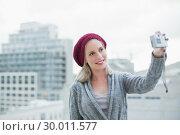Купить «Cheerful pretty blonde taking a self picture outdoors», фото № 30011577, снято 31 мая 2013 г. (c) Wavebreak Media / Фотобанк Лори
