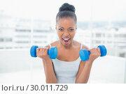Купить «Woman working out with dumbbells», фото № 30011729, снято 28 мая 2013 г. (c) Wavebreak Media / Фотобанк Лори