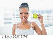 Купить «Attractive woman holding green apple», фото № 30011741, снято 28 мая 2013 г. (c) Wavebreak Media / Фотобанк Лори