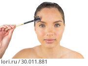 Купить «Smiling sensual woman using eyebrow brush», фото № 30011881, снято 16 мая 2013 г. (c) Wavebreak Media / Фотобанк Лори