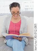 Купить «Smart woman with reading glasses sitting on sofa and reading a book», фото № 30012081, снято 16 мая 2013 г. (c) Wavebreak Media / Фотобанк Лори