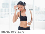 Купить «Tired dark haired model in sportswear drying herself with a towel», фото № 30012777, снято 14 июня 2013 г. (c) Wavebreak Media / Фотобанк Лори
