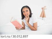 Dreamy young dark haired model reading a book. Стоковое фото, агентство Wavebreak Media / Фотобанк Лори