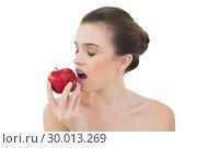 Купить «Relaxed natural brown haired model biting an apple», фото № 30013269, снято 18 июня 2013 г. (c) Wavebreak Media / Фотобанк Лори
