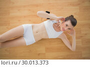 Купить «Charming fit brown haired model in sportswear listening to music», фото № 30013373, снято 18 июня 2013 г. (c) Wavebreak Media / Фотобанк Лори