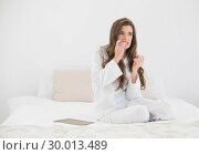 Worried casual brown haired woman in white pajamas sitting on her bed. Стоковое фото, агентство Wavebreak Media / Фотобанк Лори