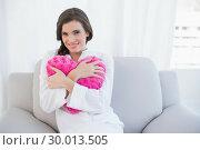 Купить «Delighted casual brown haired woman in white pajamas hugging a heart shaped pillow», фото № 30013505, снято 18 июня 2013 г. (c) Wavebreak Media / Фотобанк Лори