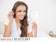 Купить «Smiling attractive brunette applying mascara and holding mirror», фото № 30013841, снято 19 июня 2013 г. (c) Wavebreak Media / Фотобанк Лори