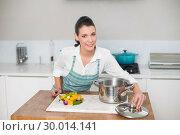 Купить «Content pretty woman wearing apron cooking», фото № 30014141, снято 20 июня 2013 г. (c) Wavebreak Media / Фотобанк Лори