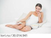 Купить «Attentive young brown haired model eating popcorn while watching tv», фото № 30014941, снято 25 июня 2013 г. (c) Wavebreak Media / Фотобанк Лори