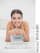 Купить «Casual young brown haired model in white pajamas reading a newspaper», фото № 30014981, снято 25 июня 2013 г. (c) Wavebreak Media / Фотобанк Лори